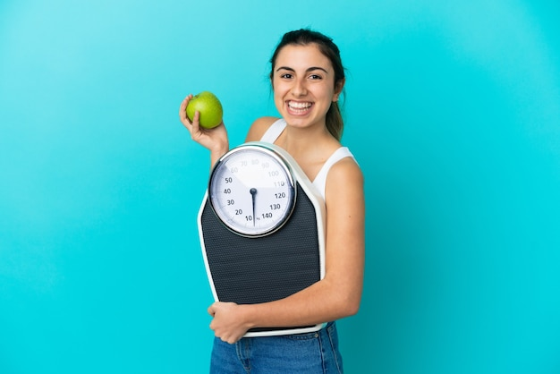 Молодая кавказская женщина изолирована на синем фоне с весами и яблоком