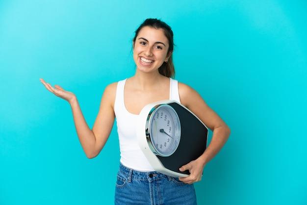 기계 무게와 파란색 배경에 고립 된 젊은 백인 여자