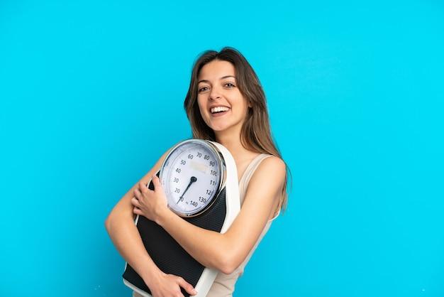 무게 기계와 파란색 배경에 고립 된 젊은 백인 여자