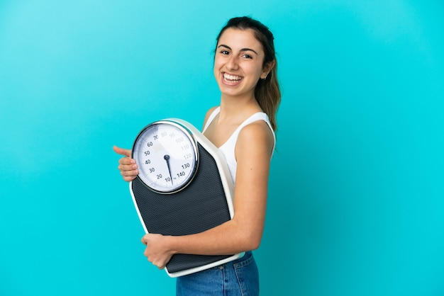 Молодая кавказская женщина изолирована на синем фоне с весами
