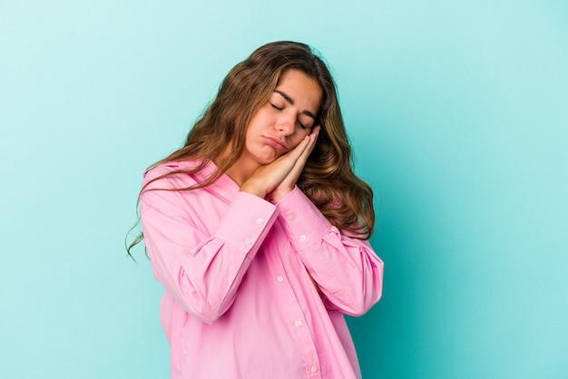 手で口を覆う疲れたジェスチャーを示すあくびをしている青い背景に分離された若い白人女性。