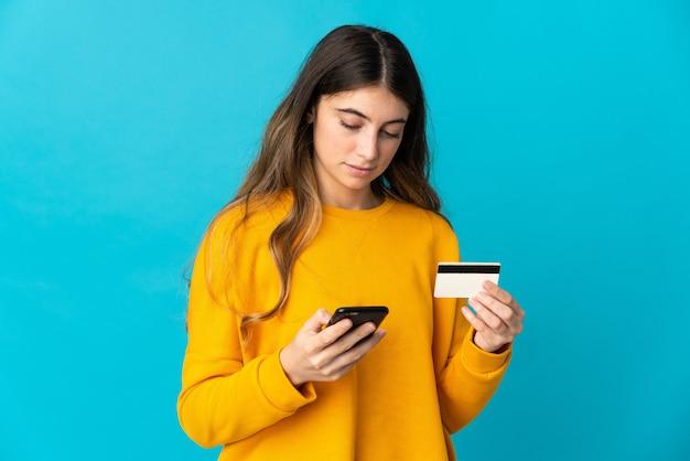 クレジットカードで携帯電話で青い購入に孤立した若い白人女性