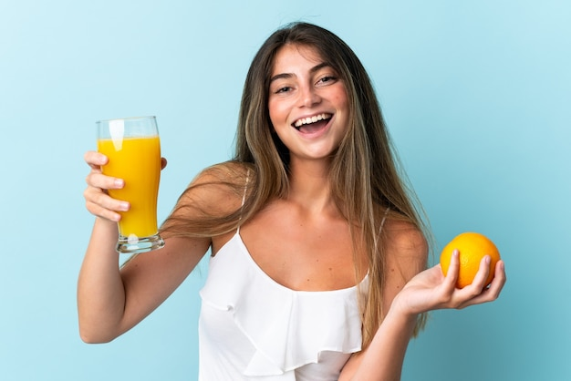 オレンジとオレンジジュースを保持している青に分離された若い白人女性