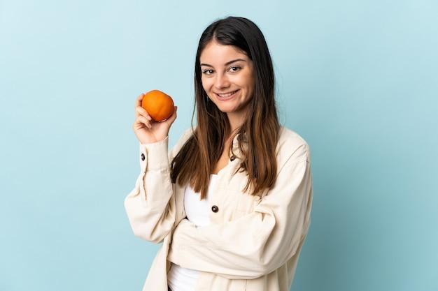 オレンジ色を保持している青に分離された若い白人女性