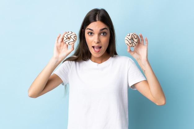 파란색 도넛을 들고 놀란에 고립 된 젊은 백인 여자