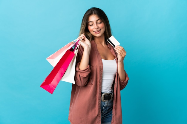 ショッピングバッグとクレジットカードを保持している青に分離された若い白人女性