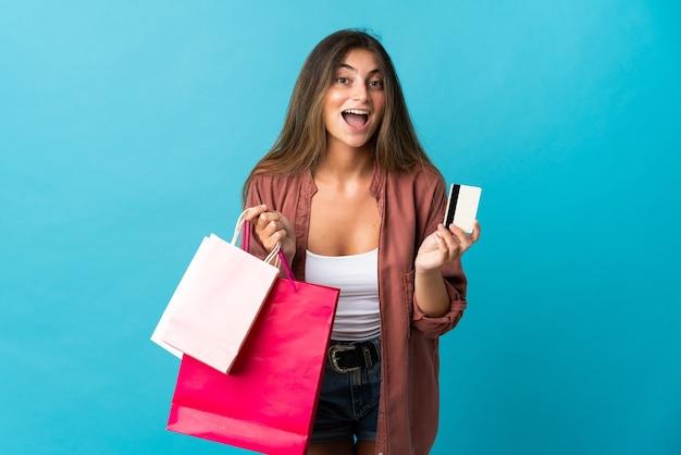 買い物袋を持って青に孤立し、驚いた若い白人女性