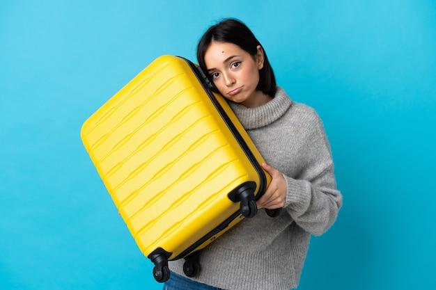 旅行スーツケースと不幸な休暇で青に孤立した若い白人女性