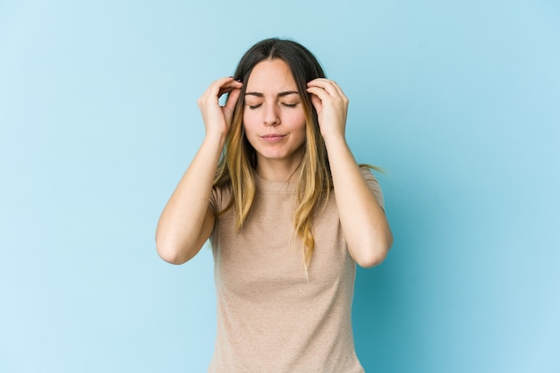 こめかみに触れて頭痛を抱えている青い空間に孤立した若い白人女性。