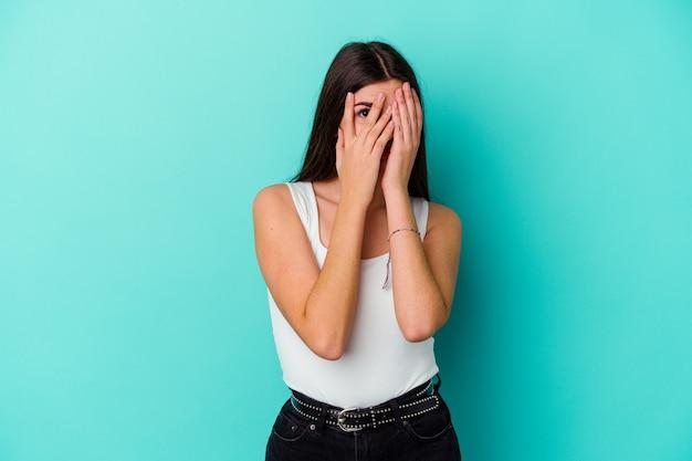 파란색 벽에 고립 된 젊은 백인 여자는 두려워 하 고 긴장하는 손가락을 통해 깜박입니다.
