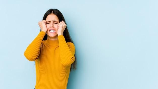 泣いている、何か、苦しみ、混乱の概念に不満の青い壁に分離された若い白人女性。