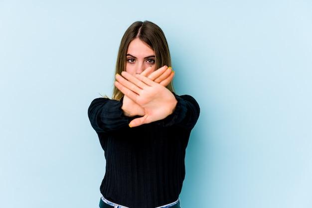 Молодая кавказская женщина изолирована на синей стене, делая жест отрицания