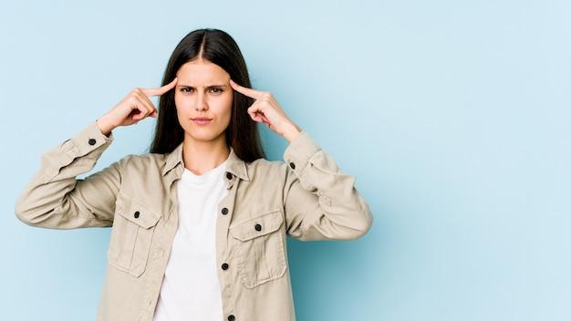 青い壁に分離された若い白人女性は、人差し指を頭に向けて、タスクに焦点を当てた。