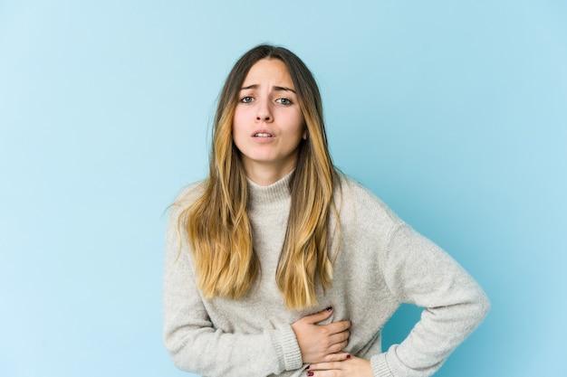 Молодая кавказская женщина изолирована на синей стене с болью в печени, болит живот.