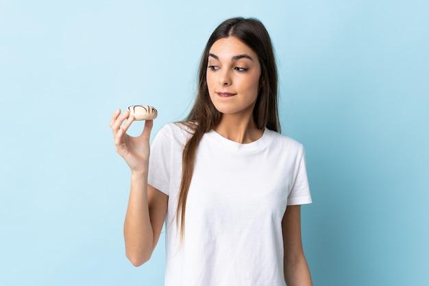 ドーナツを保持している青い壁に分離された若い白人女性