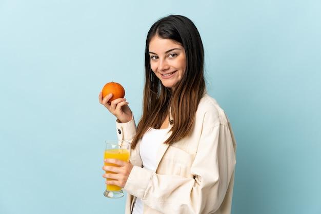 オレンジとオレンジジュースを保持している青い壁に分離された若い白人女性