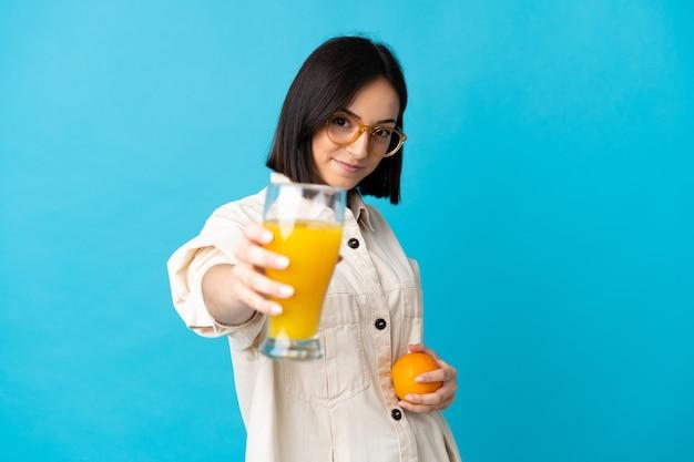 Молодая кавказская женщина изолирована на синей стене, держа апельсин и апельсиновый сок