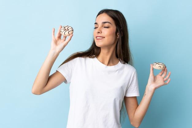 幸せな表情でドーナツを保持している青い壁に分離された若い白人女性