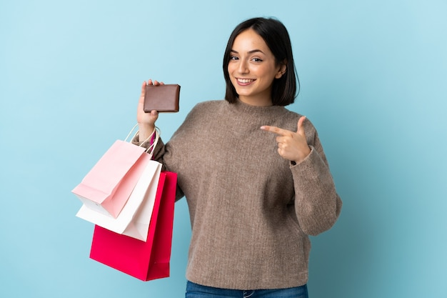 쇼핑백과 신용 카드를 들고 파란색 벽에 고립 된 젊은 백인 여자
