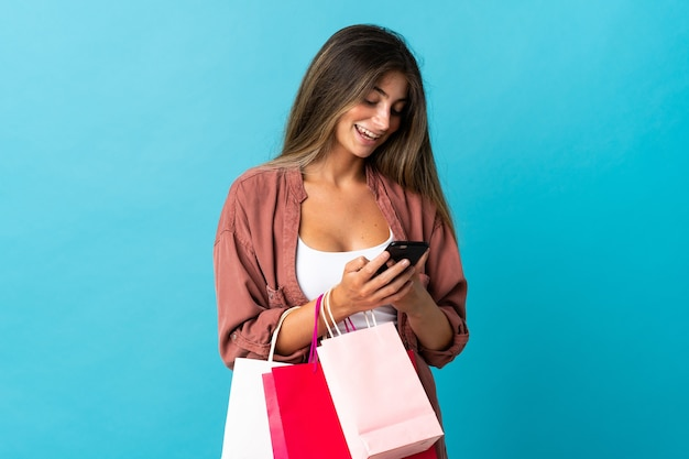 파란색 벽에 쇼핑백을 들고 친구에게 그녀의 휴대 전화로 메시지를 쓰는 젊은 백인 여자