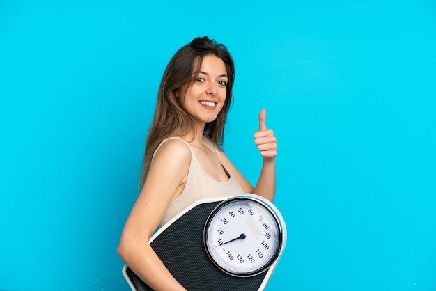 Молодая кавказская женщина изолирована на синей стене, держа весы с большим пальцем вверх