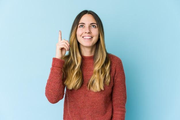 파란색 벽에 고립 된 젊은 백인 여자는 빈 공간을 보여주는 두 앞 손가락으로 나타냅니다.