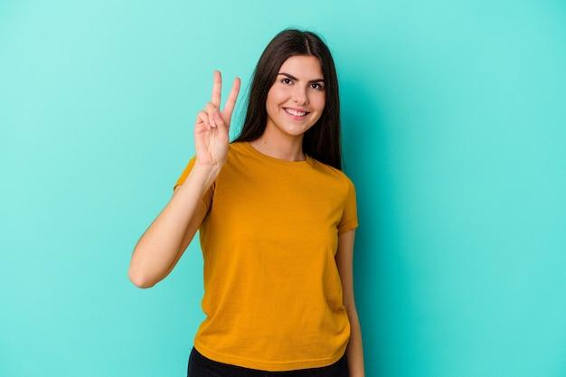 指で平和のシンボルを示す、楽しくてのんきな青い壁に隔離された若い白人女性。