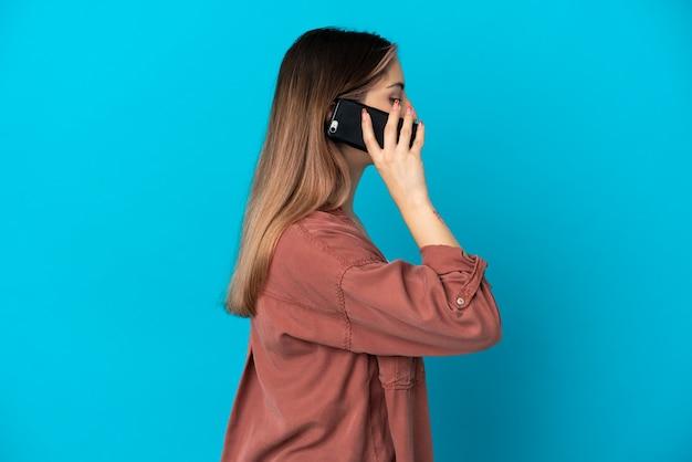 누군가와 휴대 전화로 대화를 유지하는 파란색 벽에 고립 된 젊은 백인 여자