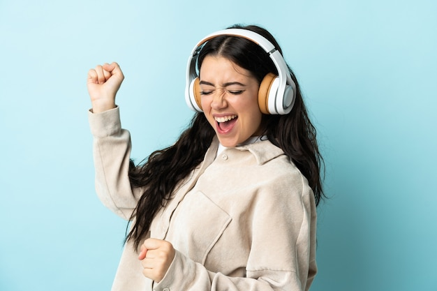 Молодая кавказская женщина изолирована на синей стене, слушает музыку и танцует