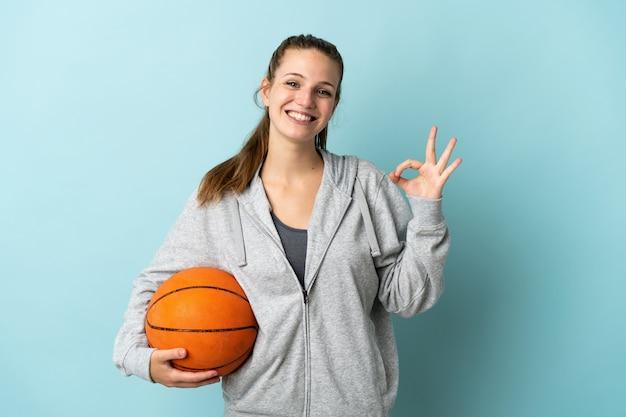 농구를하고 확인 서명을 만드는 파란색 벽에 고립 된 젊은 백인 여자