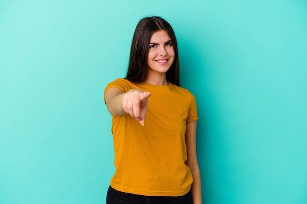 손가락으로 앞을 가리키는 파란색 벽에 고립 된 젊은 백인 여자
