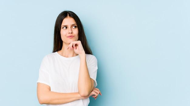 青い壁に分離された若い白人女性は、コピースペースを見て何かを考えてリラックスしました。