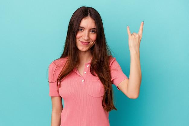 指でロックジェスチャーを示す青い壁に分離された若い白人女性