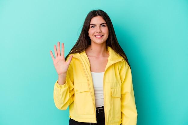 Молодая кавказская женщина изолирована на синей стене, улыбаясь веселой показывая номер пять пальцами