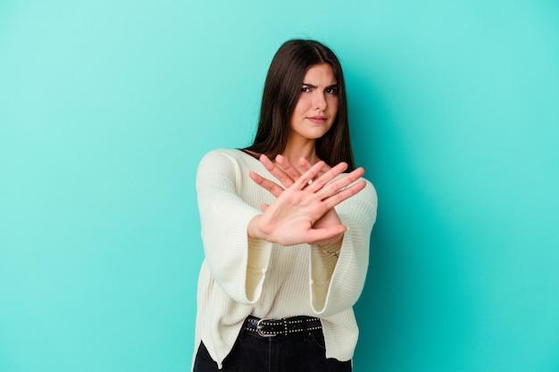 당신을 방지하는 정지 신호를 보여주는 뻗은 손으로 파란색 벽 서에 고립 된 젊은 백인 여자.