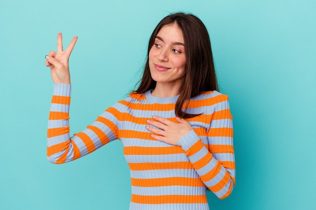 젊은 백인 여자 가슴에 손을 넣어 맹세를 복용 파란색 벽에 고립.