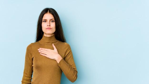 Молодая кавказская женщина изолированная на голубой стене принимая присягу, кладя руку на комод.
