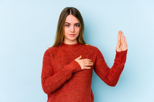 Молодая кавказская женщина изолирована на голубой стене принимая присягу, положив руку на грудь.