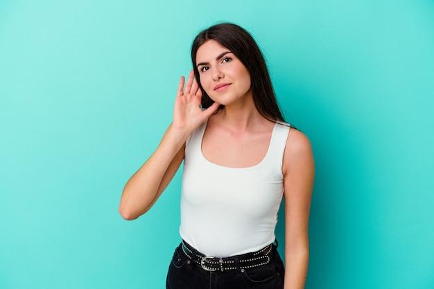 젊은 백인 여자는 험담을 듣고 파란색 벽에 고립.