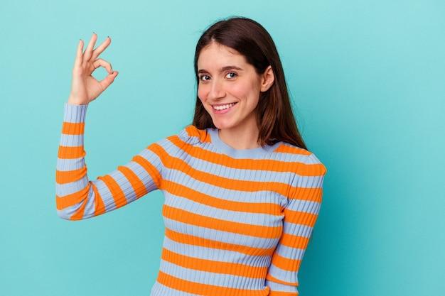 파란색 벽에 고립 된 젊은 백인 여자는 눈을 윙크 하 고 손으로 괜찮아 제스처를 보유하고있다.