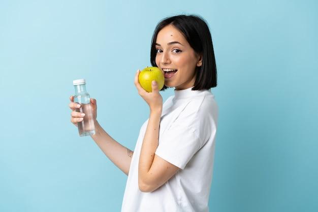 사과와 물 한 병 파란색 벽에 고립 된 젊은 백인 여자