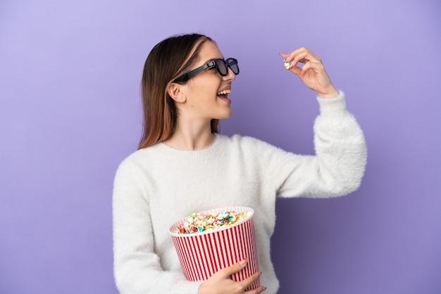 Молодая кавказская женщина изолирована на синем в 3d-очках и держит большое ведро попкорна