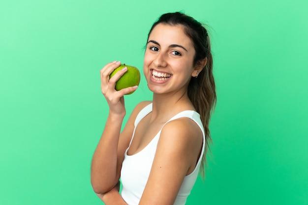 사과 먹는 녹색 배경에 고립 된 젊은 백인 여자