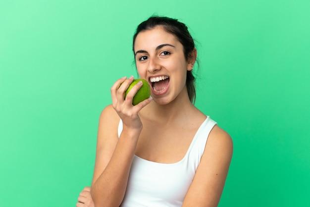 リンゴを食べる緑の背景に分離された若い白人女性