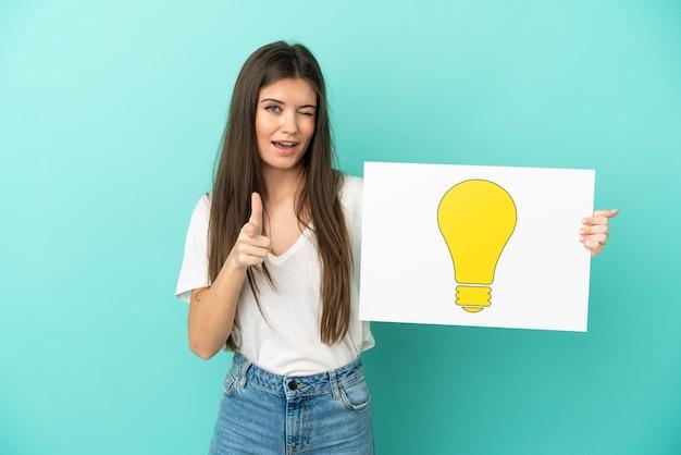 Молодая кавказская женщина изолирована, держа плакат со значком лампочки и указывая вперед