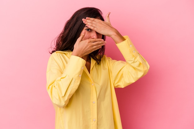 ピンクの背景で隔離された若い白人女性は、恥ずかしい顔を覆って、指を通してカメラで点滅します。