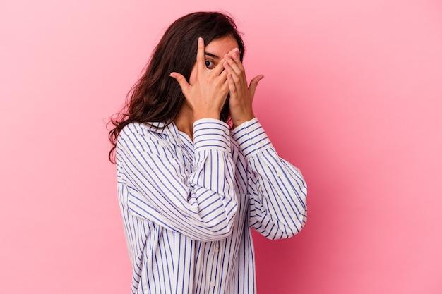 ピンクの背景に分離された若い白人女性は、おびえ、神経質な指を点滅します。