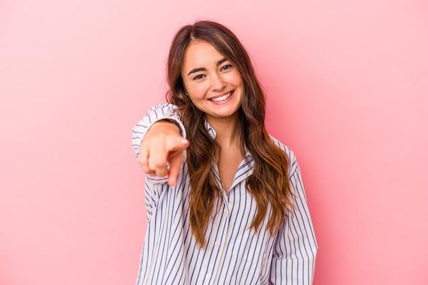 ピンクの背景に孤立した若い白人女性は、正面を指している陽気な笑顔。