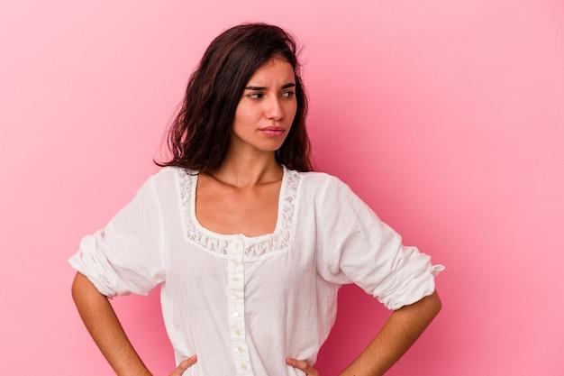 ピンクの背景に孤立した若い白人女性は混乱し、疑わしく、不安を感じています。