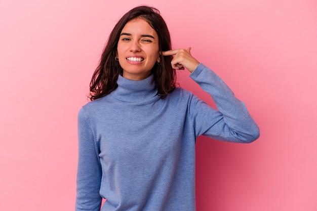 분홍색 배경에 고립된 젊은 백인 여성은 큰 소리로 스트레스를 받고 필사적으로 귀를 덮고 있습니다.